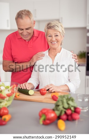 Happy Senior Couple Preparing Healthy Recipe with Fresh Vegetables at the Kitchen, While Wife Looking at the Camera.