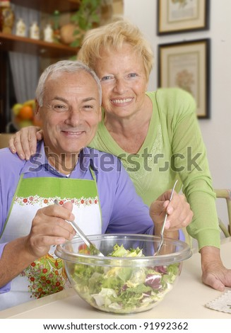 Happy senior couple preparing vegetable salad in the kitchen.