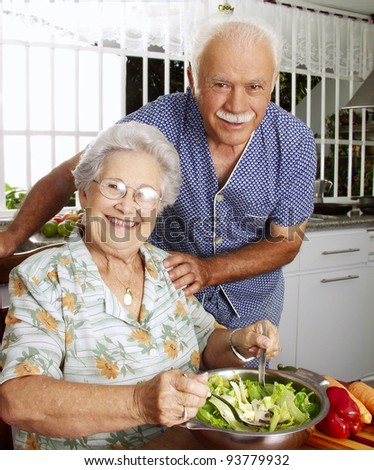 Happy senior couple preparing vegetable salad in the kitchen. Grandparents at kitchen preparing vegetable salad. - stock photo