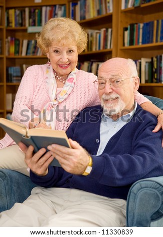 Happy senior couple reading together at the library.