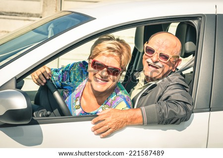 Happy senior couple ready for driving a car on a journey trip - Concept of joyful active elderly lifestyle with man and woman enjoying their best years - stock photo