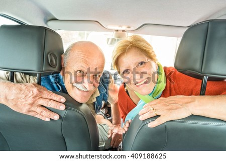 Happy senior couple ready for driving car on journey trip - Concept of joyful active elderly with retired man and woman enjoying their best years - Modern mature travel lifestyle during retirement - stock photo