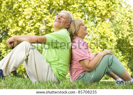 Happy senior couple relaxed on green grass back to back. - stock photo