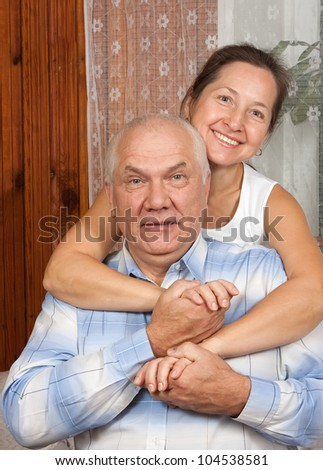 Happy senior couple relaxing at home on sofa