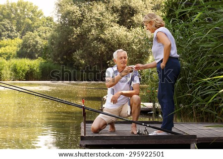 Happy senior couple relaxing at lakeside. Senior man squatting on the pier while her wife gives him a cup of coffee. Elderly people have fun.