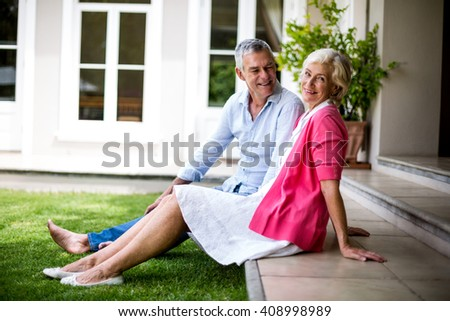 Happy senior couple relaxing on steps outside house - stock photo