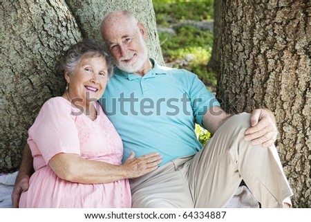 Happy senior couple relaxing outdoors. - stock photo