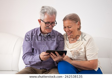 Happy senior couple relaxing together and using a digital tablet - stock photo