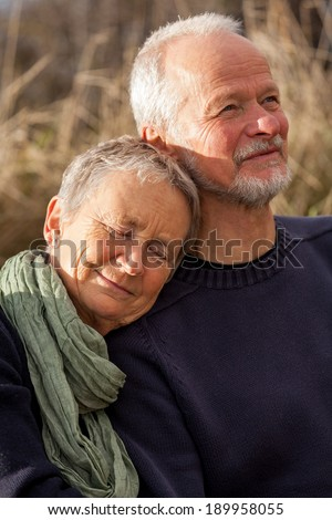 happy senior couple relaxing together in the sunshine on a wooden bench in the countryside with the one reclining full length on the seat with his head on his partners lap