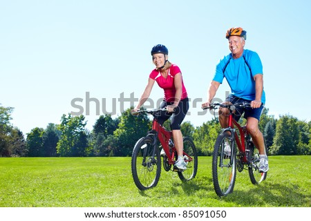 Happy senior couple  riding  in the park. - stock photo