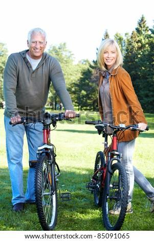 Happy senior couple  riding  in the park. - stock photo