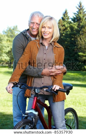 Happy senior couple  riding  in the park.