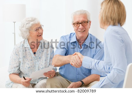 Happy senior couple sealing with an handshake a contract for the retirement - stock photo