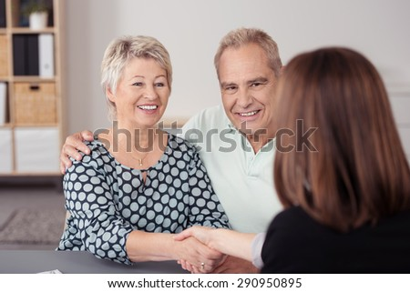 Happy Senior Couple Shaking Hands with Female Financial Agent at the Table While Making a Deal. - stock photo