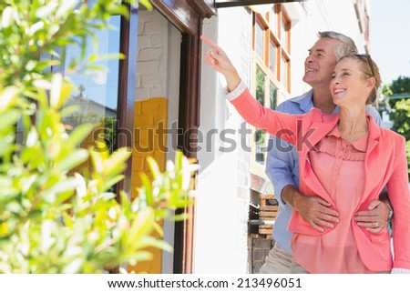 Happy senior couple shopping and pointing in the city on a sunny day - stock photo