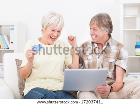 Happy Senior Couple Shopping Online Using Laptop With Credit Card - stock photo