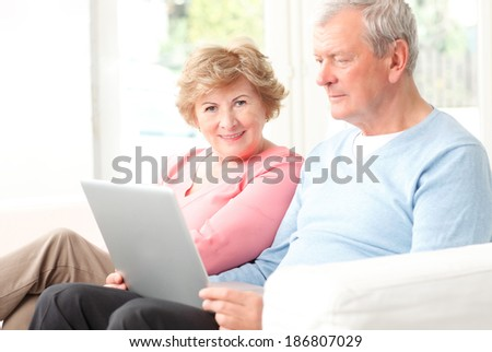 Happy senior couple sitting at desk and planning for retirement at home.