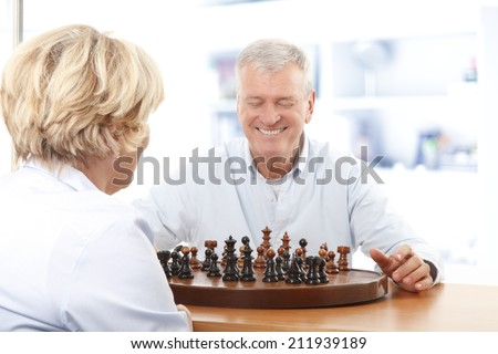 Happy senior couple sitting at desk and playing chess at home. Leisure activity at nursing home.  - stock photo