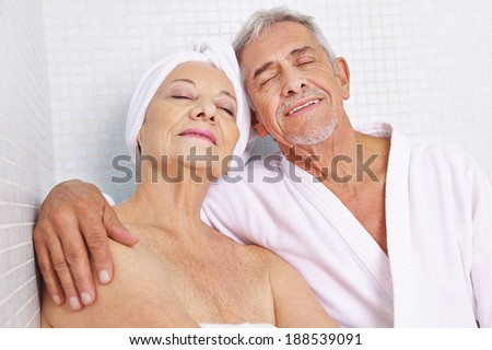 Happy senior couple sitting in relaxation room after sauna session in spa - stock photo