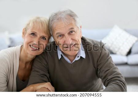 Happy senior couple sitting in sofa - stock photo