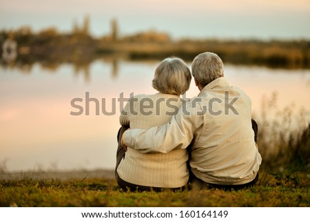 Happy senior couple sitting in summer near lake during sunset - stock photo