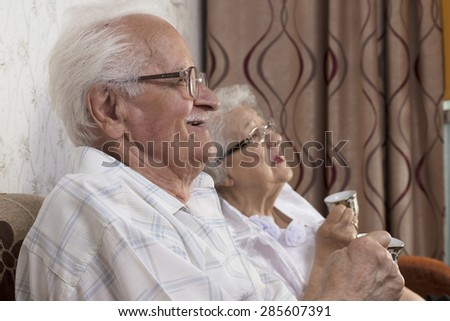 Happy senior couple sitting in their house and talking - stock photo