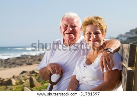 happy senior couple sitting on beach bench - stock photo