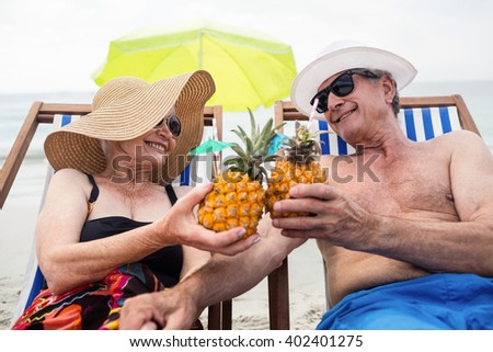 Happy senior couple sitting on deckchairs while toasting pineapple cocktail on the beach - stock photo