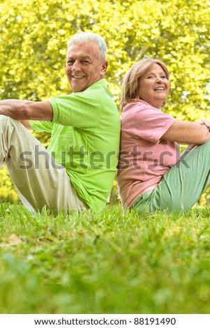 Happy senior couple sitting on grass back to back. - stock photo