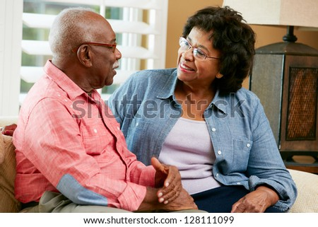 Happy Senior Couple Sitting On Sofa At Home