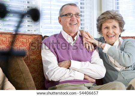 Happy senior couple sitting together on couch in living room - stock photo