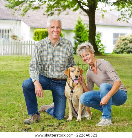 Happy senior couple sitting with labrador retriever dog in a garden - stock photo