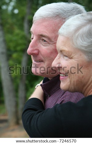 Happy Senior Couple smiling outside - stock photo