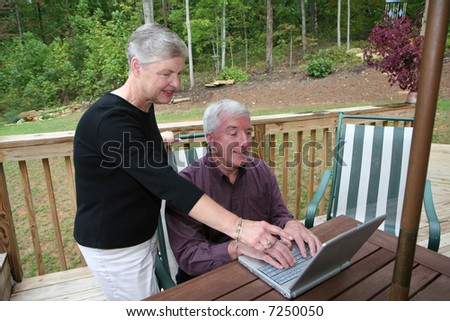 Happy Senior Couple smiling outside on computer - stock photo