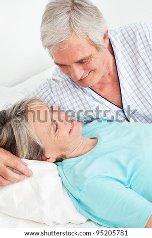 Happy senior couple smiling together in bed in the bedroom - stock photo