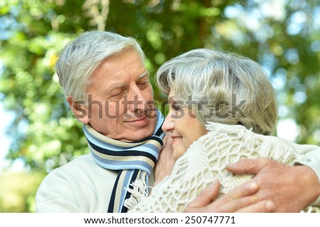 Happy senior couple standing in park - stock photo