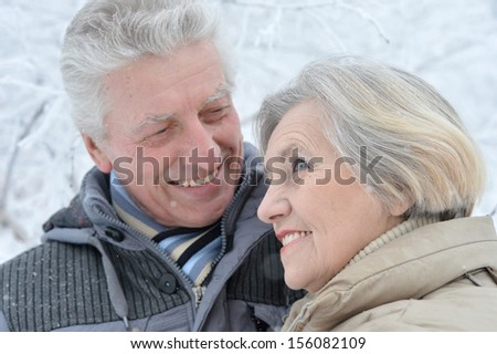 Happy senior couple standing in winter outdoors