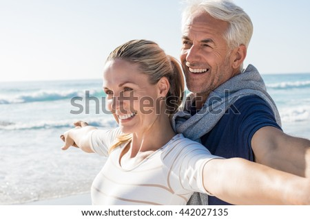 Happy senior couple standing on beach with arms outstretched and looking away. Happy couple at beach on a bright sunny day. Retired husband and smiling wife thinking about their future. - stock photo