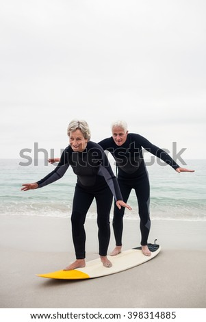 Happy senior couple surfing on surfboard on a sunny day - stock photo