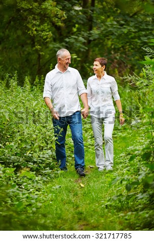 Happy senior couple taking a walk in nature in summer