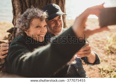 Happy senior couple taking their self portrait with their cell phone on camping day. Man and woman sitting together outdoors at campsite and taking selfie. - stock photo