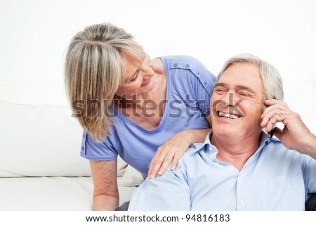 Happy senior couple talking in cell phone at home