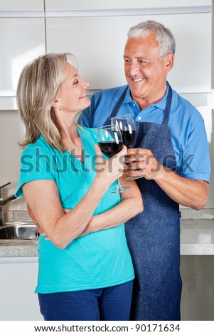 Happy senior couple toasting wine glasses in the kitchen - stock photo