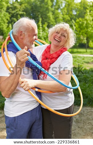 Happy senior couple together in a hoop in summer - stock photo