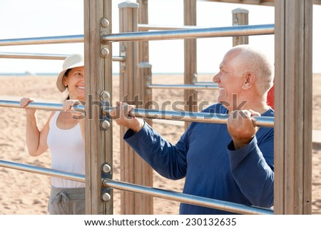 Happy senior couple together training on pull-up bar at playground in summer - stock photo