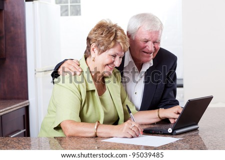 happy senior couple using internet banking checking bank balance - stock photo