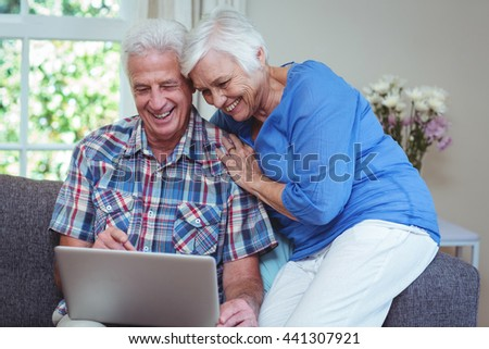 Happy senior couple using laptop at home - stock photo