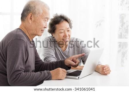 happy Senior Couple Using Laptop in living room - stock photo