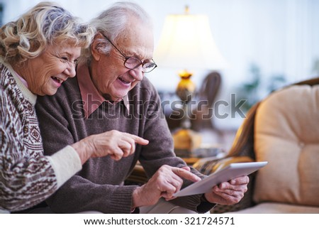 Happy senior couple using touchpad at home