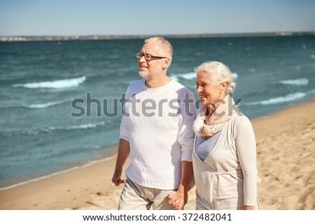happy senior couple walking along summer beach - stock photo